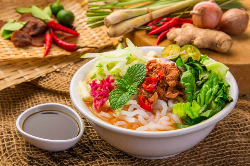assam-laksa-in-front-of-sauce-and-ingredients